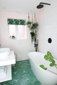 """Bathroom with green and white floor tiles, a white freestanding bath and hanging house plants in the corner"""