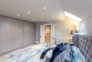 """A master bedroom with an en suite bathroom in grey and blue tones"""