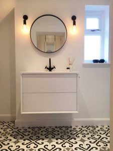 alt=a monochrome bathroom with a white vanity unit and black taps