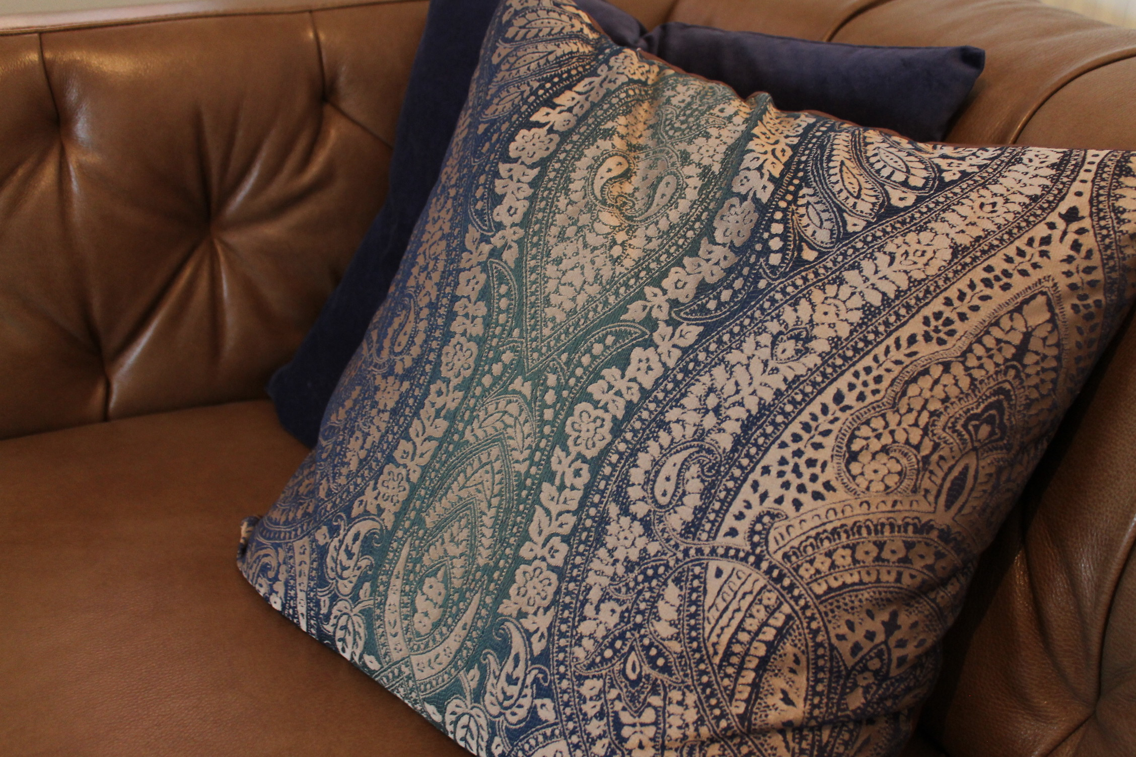 """Patterned and plain cushions in blue tones on top of a tan leather sofa"""