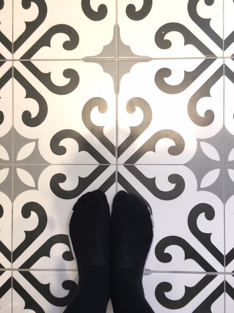 "alt= ""Feet in black socks on patterned tiles"""