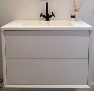 alt= a white bathroom vanity unit with black taps