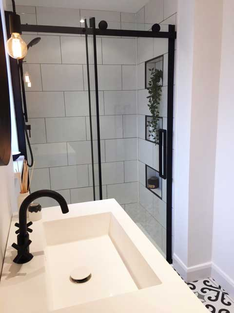 alt= a contemorary monochrome bathroom with black taps and shower fittings""