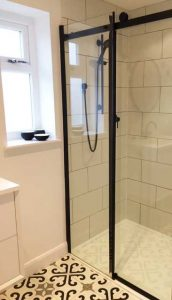 alt= a black sliding shower screen with a black shower""