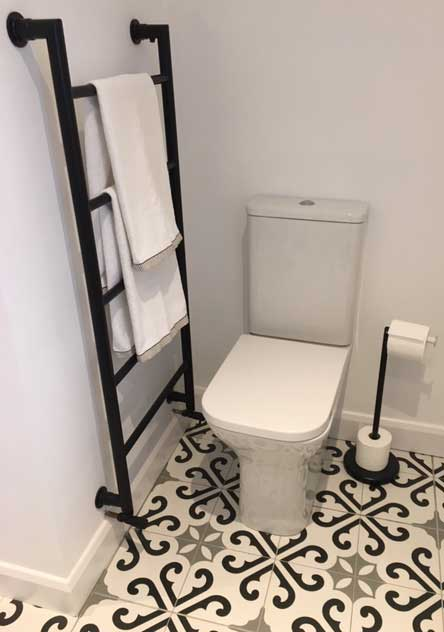 "alt= ""White toilet next to black towel radiator with a patterned tile floor"""