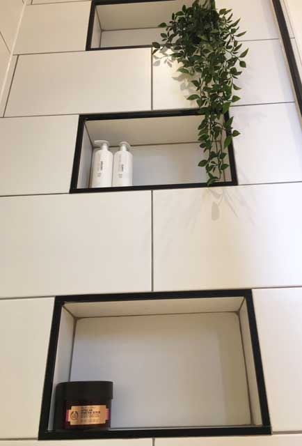 """alt=""""Tiled shower alcoves with black tile trim by Three Interiors"""""""