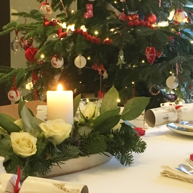 """a Christmas table decoration with a candle and a decorated Christmas tree in the background"""