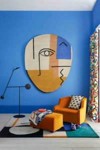 A living room with an abstract style rug on the wall with bold blue paint and patterned curtainss