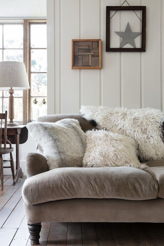 A velvet chair piled with sheepskin and shaggy cushions with a panelled wall in the background