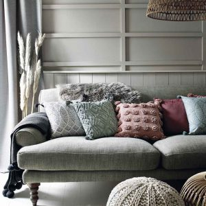 A grey linen sofa piled with cushions and throws