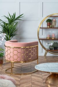 An occasional chair in brass and rose pink velvet sits in a panelled room with chevron wood flooring