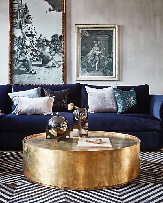 A large round brass coffee table sits in front of a deep blue velvet sofa piled with cushions