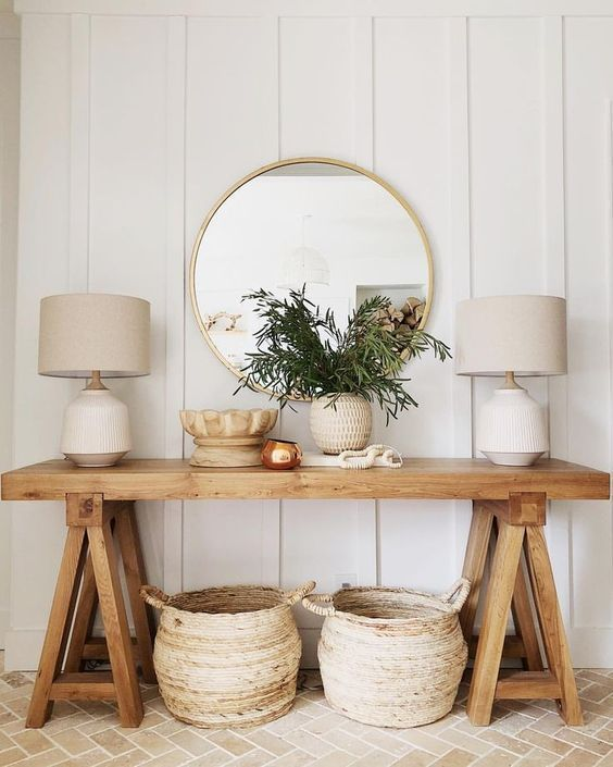 Wooden console table in front of a panelled wall with two lamps sat on top of it